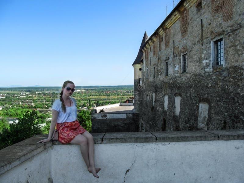 La mujer joven descalza en una blusa blanca y una falda roja se está sentando en el balcón del castillo de Palanok Bastante tur imagen de archivo