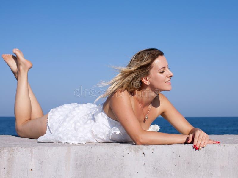 La mujer joven descalza en vestido sin mangas blanco corto toma el sol w fotos de archivo libres de regalías