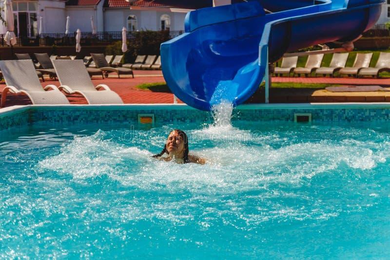 la mujer joven deslizada el waterslide en la piscina y las risas fotografía de archivo
