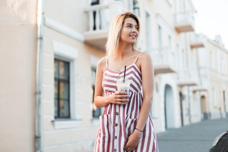 La mujer joven divertida hermosa con una sonrisa positiva en un vestido elegante rosado con las rayas se coloca cerca de un edifi imagen de archivo