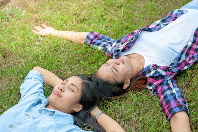 La mujer joven dos, muchacha hermosa está relajando la mentira en la hierba i fotografía de archivo libre de regalías