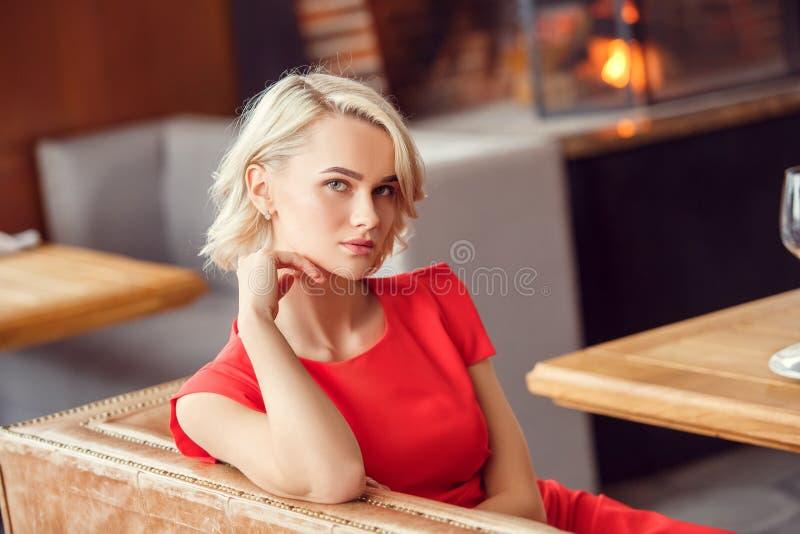 La mujer joven el fecha en el restaurante que se sentaba mirando la sonrisa de la cámara se relajó foto de archivo