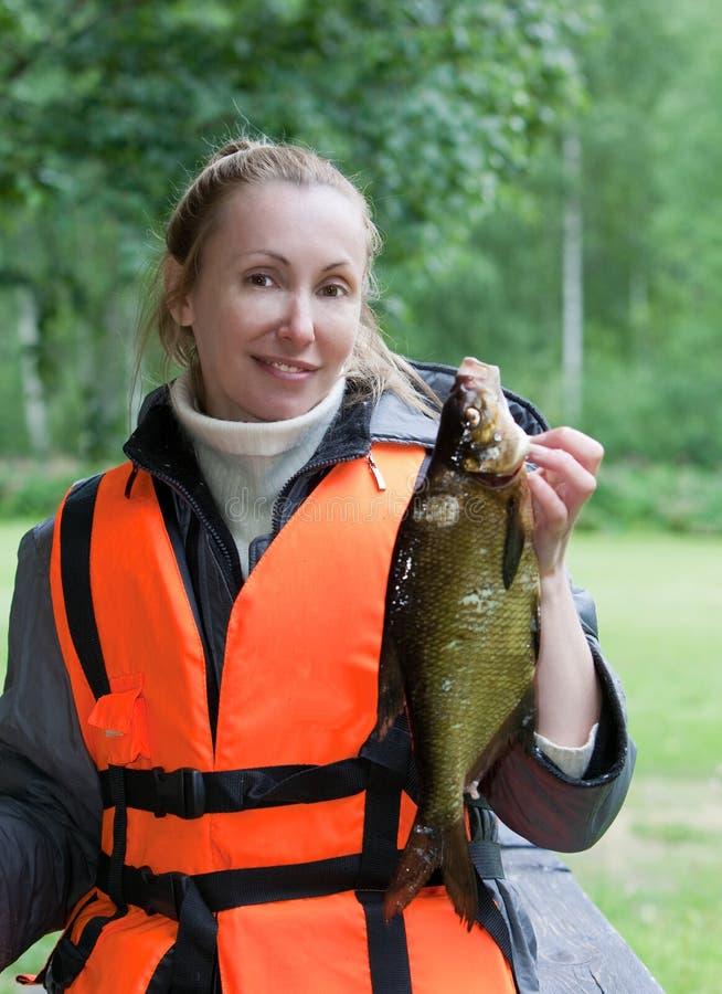 La mujer joven el pescador con cogió la brema fotos de archivo libres de regalías