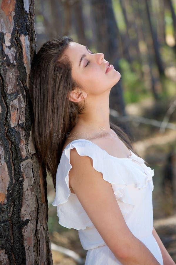 La mujer joven elegante con los ojos se cerró en el bosque imagenes de archivo
