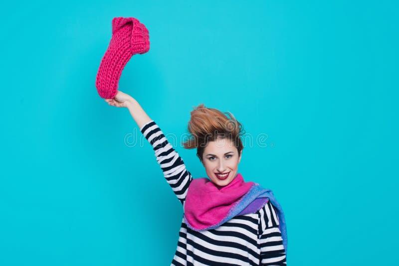 La mujer joven elegante quita un sombrero rosado hecho punto de su cabeza en el estudio en un fondo azul Invierno adiós El resort imagen de archivo libre de regalías