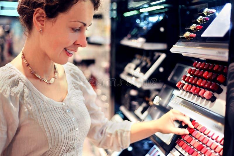 La mujer joven elige el lápiz labial en almacén fotografía de archivo libre de regalías