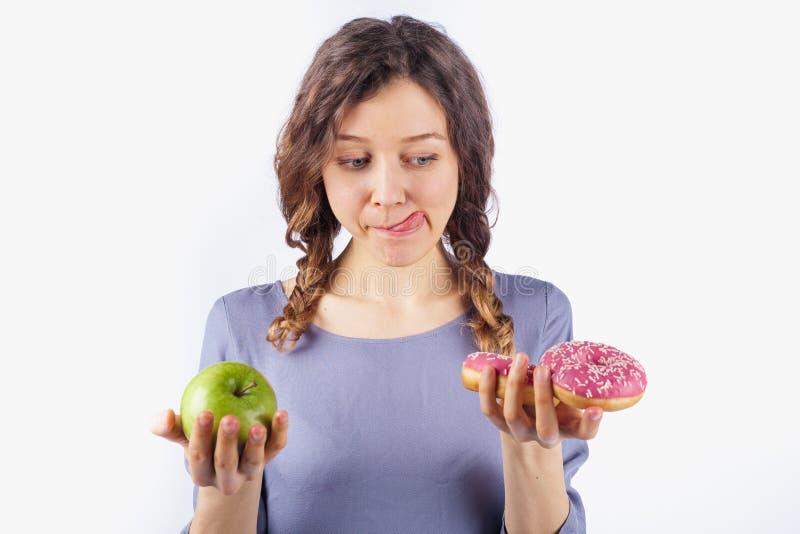 La mujer joven elige entre un buñuelo y una manzana, muchacha lame la boca Concepto de nutrición y de dieta dañinas imagen de archivo