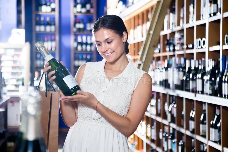 La mujer joven elige un vino en bodega imagen de archivo