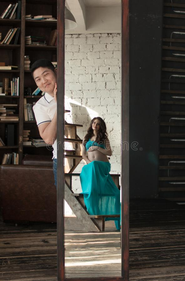 La mujer joven embarazada en un top azul y una falda se destaca cerca del espejo, miradas de un hombre de detrás un espejo imagenes de archivo