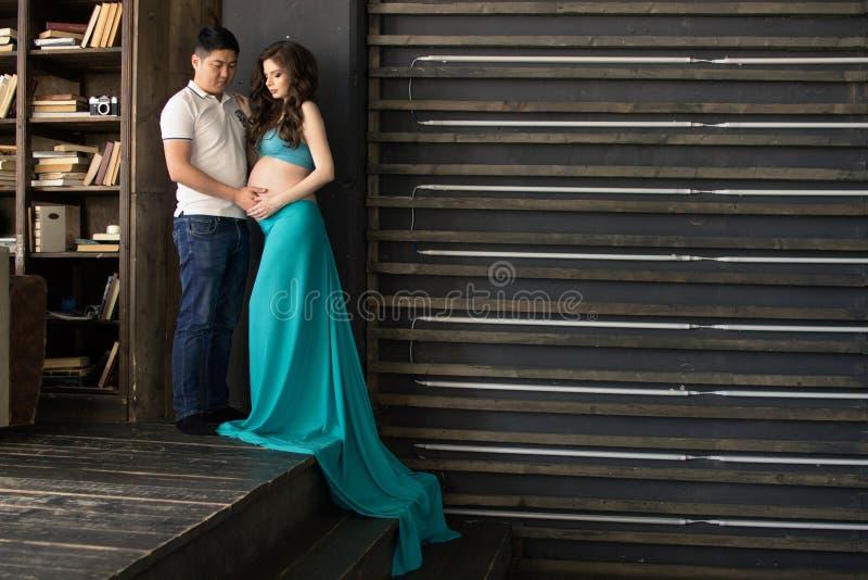 La mujer joven embarazada y un hombre se están colocando de lado a lado imagen de archivo libre de regalías