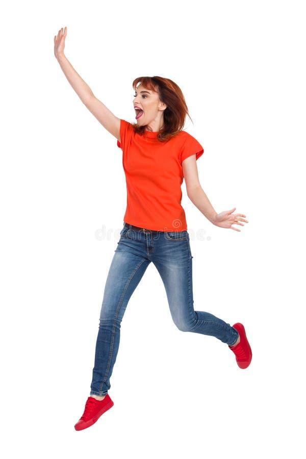 La mujer joven emocionada está saltando la mano y el grito que agitan fotos de archivo