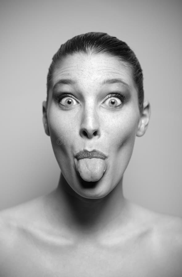 La mujer joven empuja hacia fuera su lengua fotografía de archivo libre de regalías