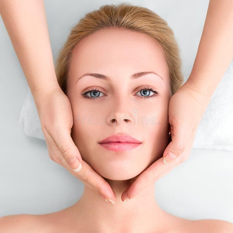 La mujer joven en balneario consigue un masaje facial foto de archivo