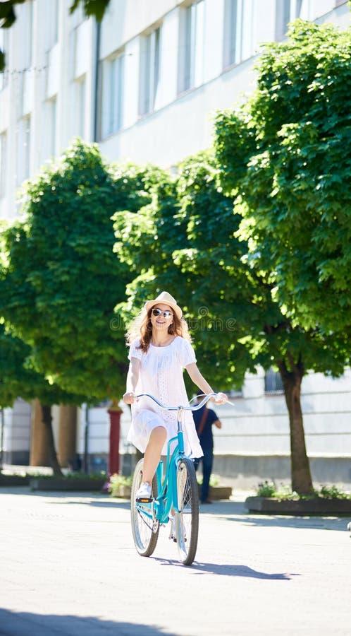 La mujer joven en la bicicleta monta el plumón solo la calle de la ciudad imagen de archivo