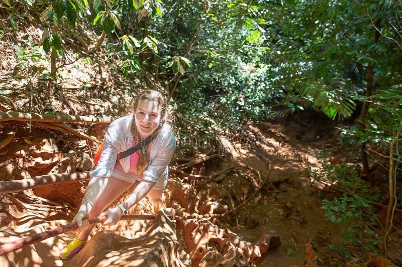 La mujer joven en blanco sube para arriba la montaña en una cuerda Visi?n desde arriba Selva tropical alrededor Ella está mirando imagenes de archivo