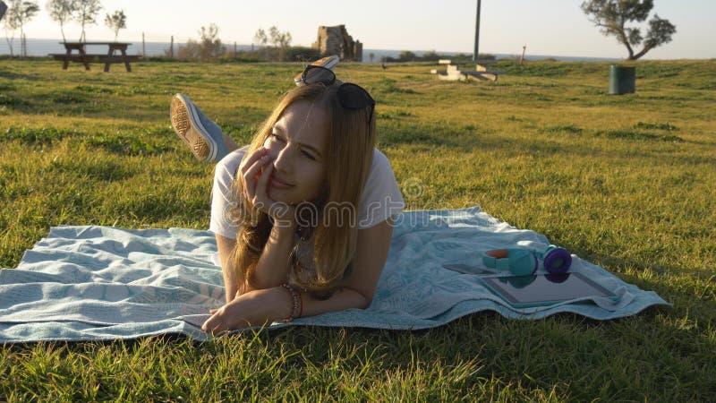 La mujer joven en buen humor pone en el parque y los sueños foto de archivo