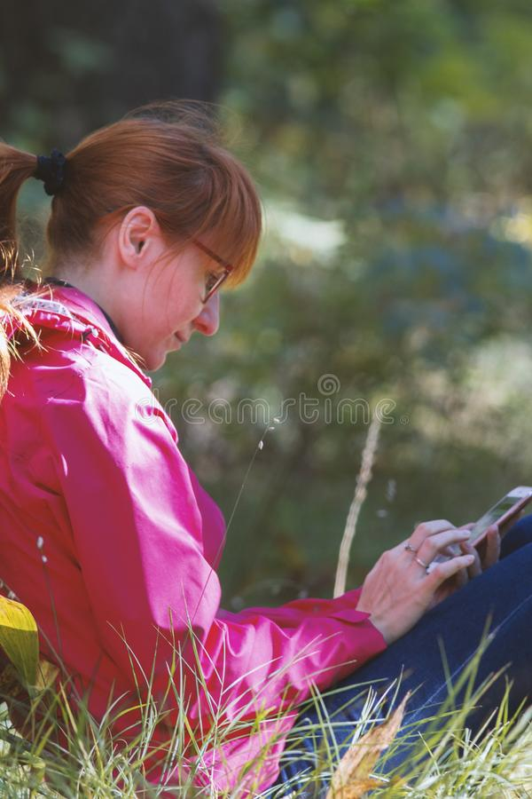 La mujer joven en chaqueta rosada utiliza el smartphone en el bosque del otoño - vertical imágenes de archivo libres de regalías