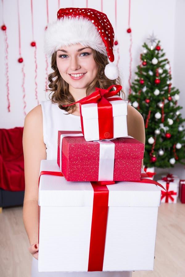 La mujer joven en el sombrero de santa con el montón de presentes acerca a la Navidad tr imagen de archivo