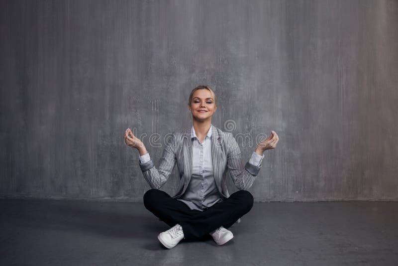 La mujer joven en el traje de negocios que se sienta en la actitud de Lotus, energía del restablecimiento, medita Salud y trabajo imágenes de archivo libres de regalías