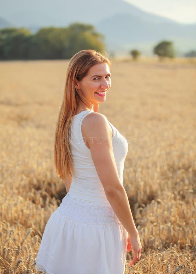La mujer joven en el vestido blanco que miraba detrás sobre su hombro, sonriendo, sol de la tarde encendió el campo de trigo detr imagen de archivo