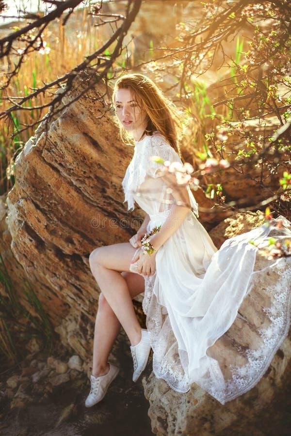 La mujer joven en el vestido blanco se está sentando en la piedra bajo ramas foto de archivo libre de regalías