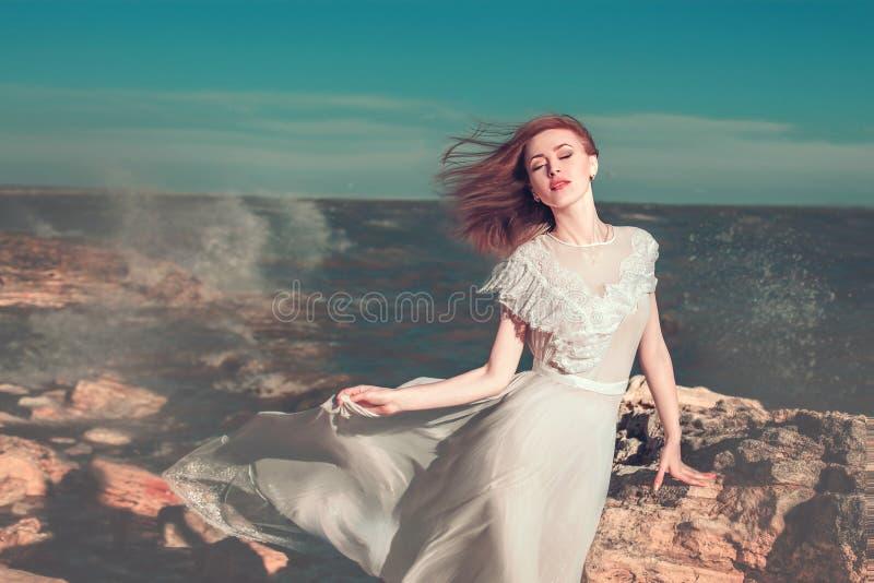 la mujer joven en el vestido que agita blanco se está colocando en la costa de mar cerca de la piedra grande fotos de archivo libres de regalías