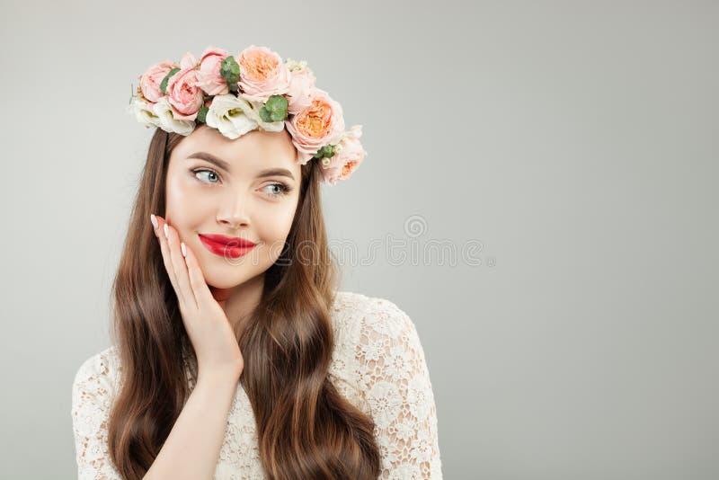 La mujer joven en flores del verano enrruella Modelo bonito con maquillaje rojo de los labios y el retrato lindo de la sonrisa foto de archivo libre de regalías