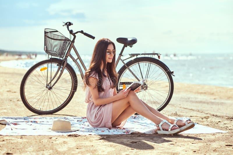La mujer joven en gafas de sol celebra un libro y la mirada de la cámara mientras que se sienta en la playa fotos de archivo libres de regalías