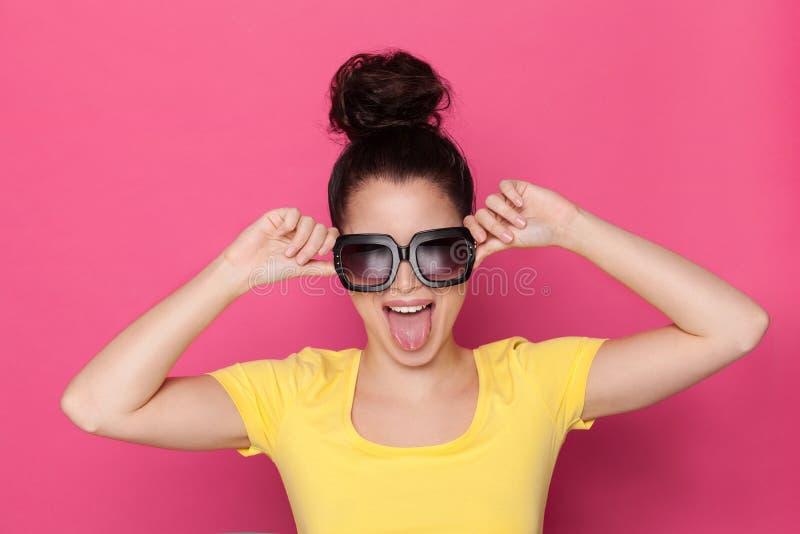 La mujer joven en gafas de sol grandes es Stickin hacia fuera machihiembra foto de archivo