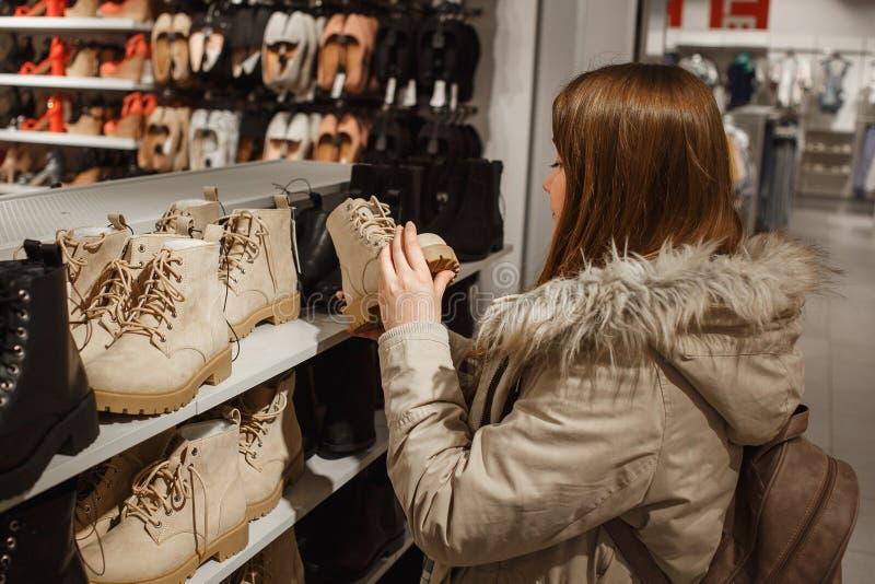 La mujer joven en invierno beige viste elegir botas beige de moda del invierno en la tienda imágenes de archivo libres de regalías
