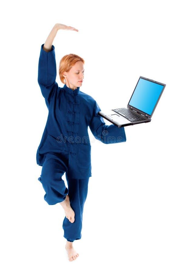 La mujer joven en kimono atiende a yoga con la computadora portátil foto de archivo