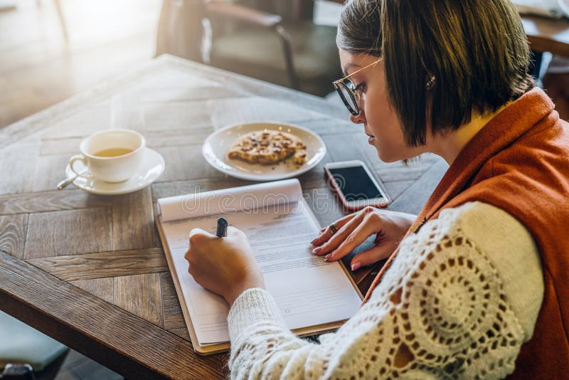 La mujer joven en lentes se está sentando en café en la tabla, firmando documentos La muchacha escribe la pluma, completa un uso fotos de archivo