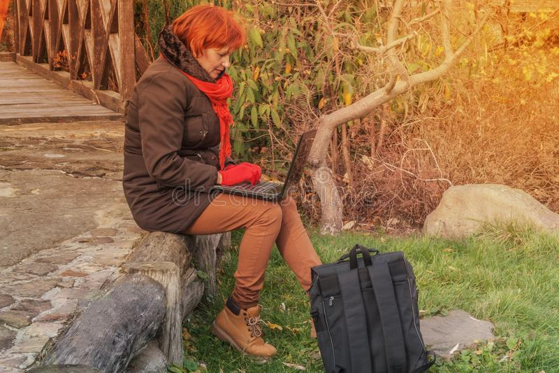 La mujer joven en parque con el ordenador portátil foto de archivo
