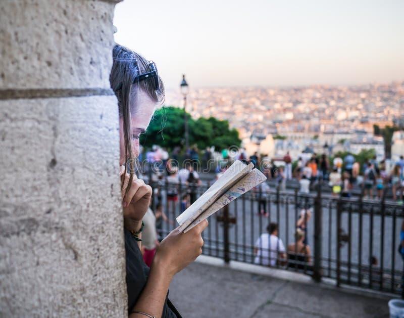 La mujer joven en perfil se inclina contra el pilar de Sacre Coeur para estudiar el mapa Tejados de París en distancia lejana fotos de archivo