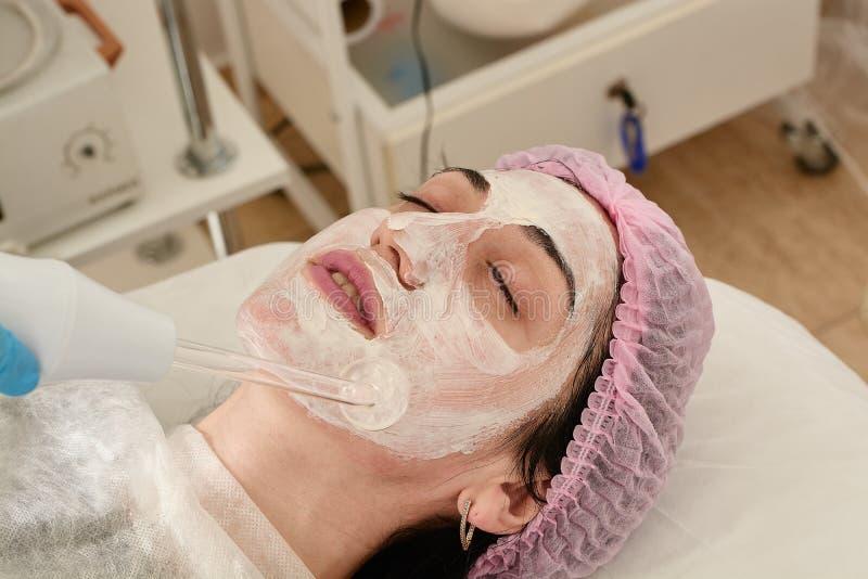 La mujer joven en salón de belleza hace rejuvenecer, entonando el procedimiento darsonval en la cara fotos de archivo