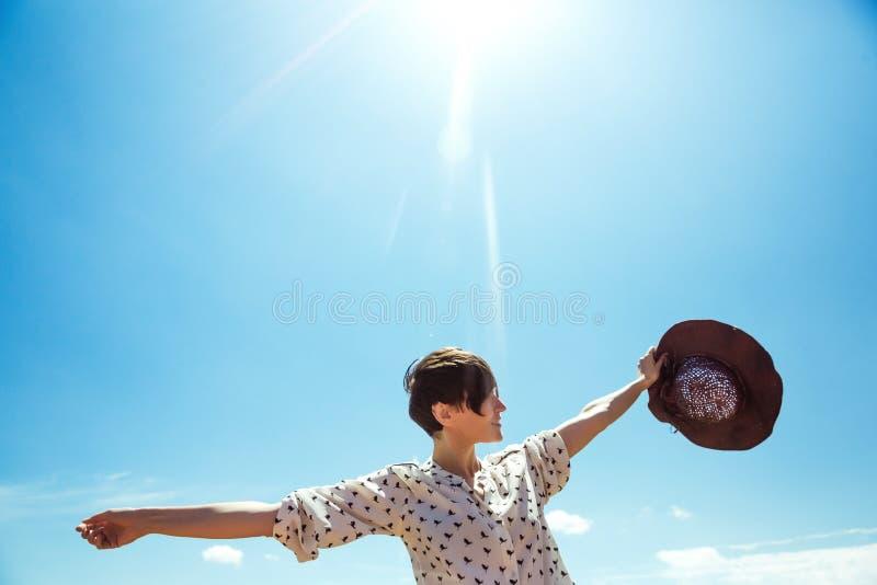 La mujer joven en sombrero que disfrutaba de tiempo de verano aumentó las manos viaja turista al aire libre de la muchacha de la  imágenes de archivo libres de regalías