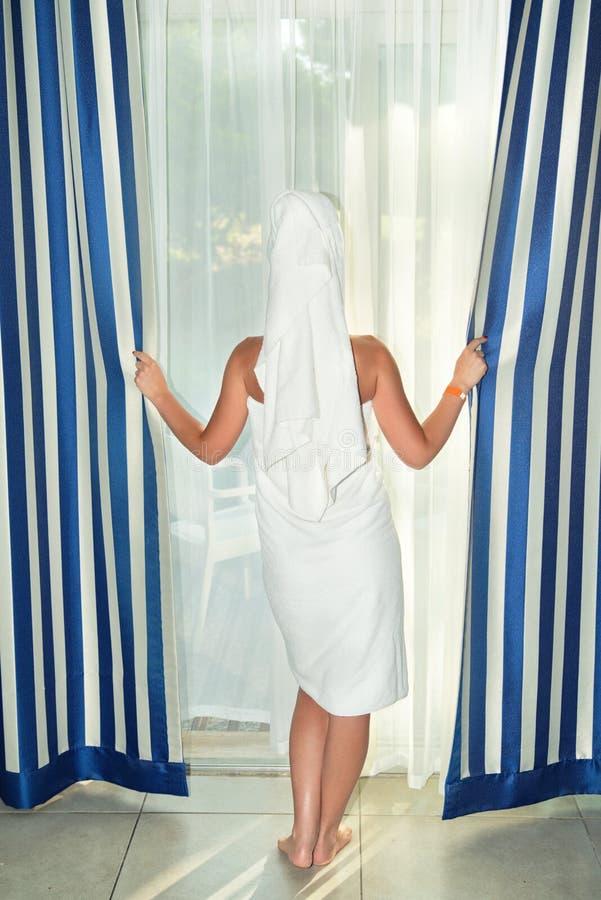 La mujer joven en toalla de baño abre las cortinas en el cuarto imagenes de archivo