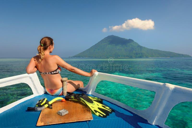 La mujer joven en traje de baño se sienta en el barco que mira a una isla fotos de archivo