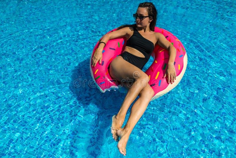 La mujer joven en traje de baño y gafas de sol miente en el anillo inflable brillante foto de archivo