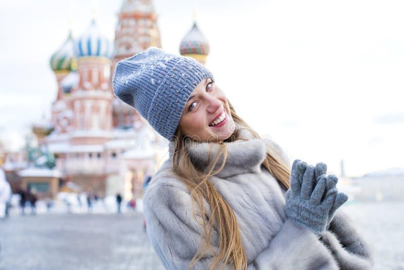La mujer joven en un azul hizo punto el sombrero y la capa de visión gris fotografía de archivo libre de regalías