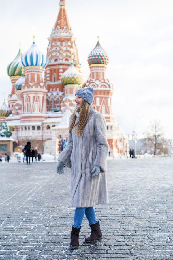 La mujer joven en un azul hizo punto el sombrero y la capa de visión gris imagen de archivo libre de regalías