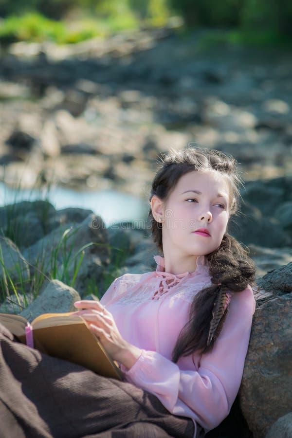 La mujer joven en un estilo de Boho es libro de lectura en la orilla del río imagen de archivo libre de regalías