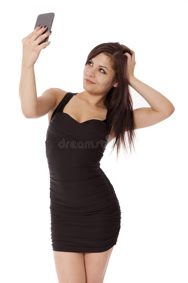 La mujer joven en un poco vestido negro toma un selfie con su célula fotos de archivo libres de regalías