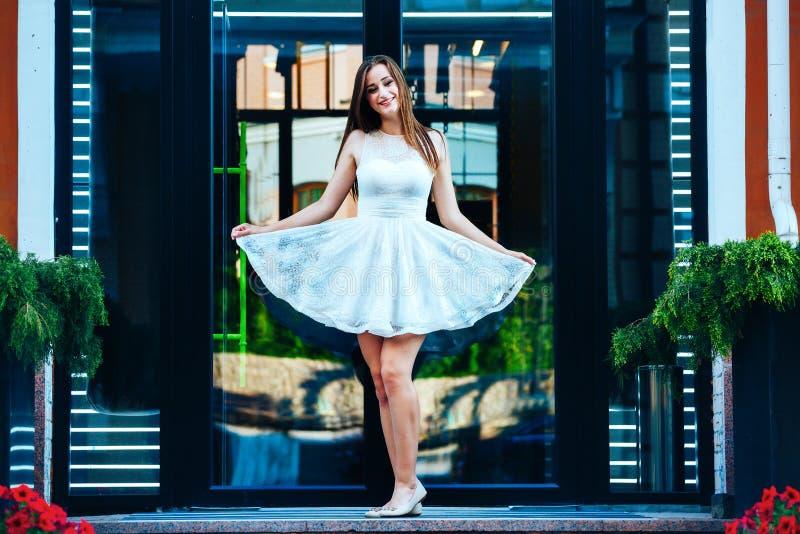 La mujer joven en un vestido blanco corto se está colocando que sostiene un vestido en manos en el fondo de una puerta de cristal fotografía de archivo