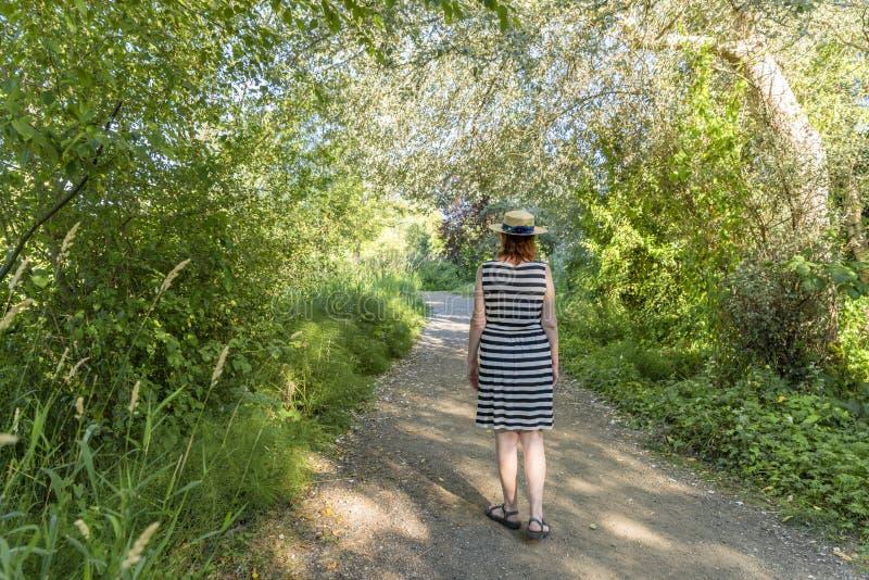 La mujer joven en un vestido rayado y un sombrero de paja camina a lo largo de una palmadita imagenes de archivo