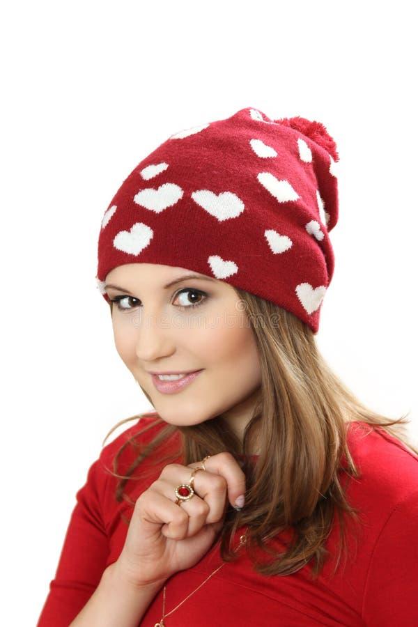 La mujer joven en un vestido rojo y un casquillo rojo con los corazones fotos de archivo libres de regalías