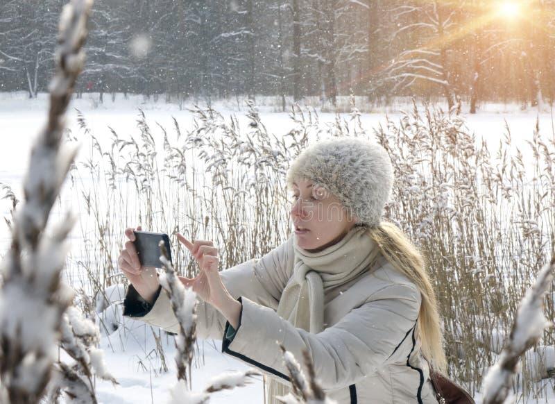 La mujer joven en una chaqueta blanca fotografía los bastones del invierno de la costa del lago del bosque en el teléfono fotos de archivo libres de regalías