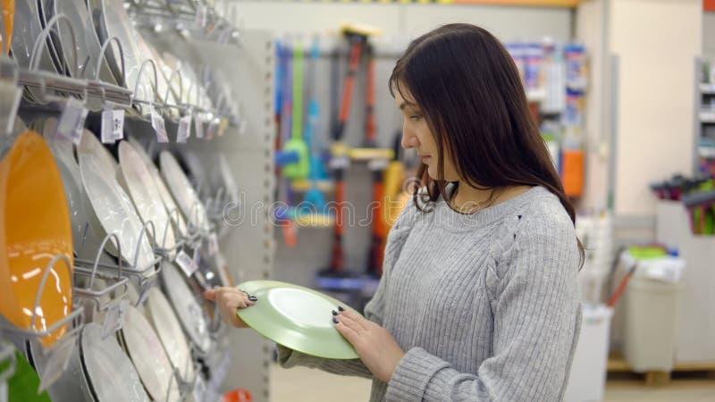 La mujer joven en una tienda de los artículos del hogar elige las placas fotografía de archivo libre de regalías