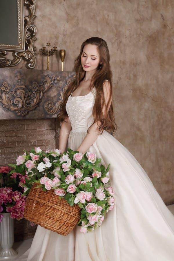 La mujer joven en vestido largo sostiene la cesta de flores foto de archivo libre de regalías
