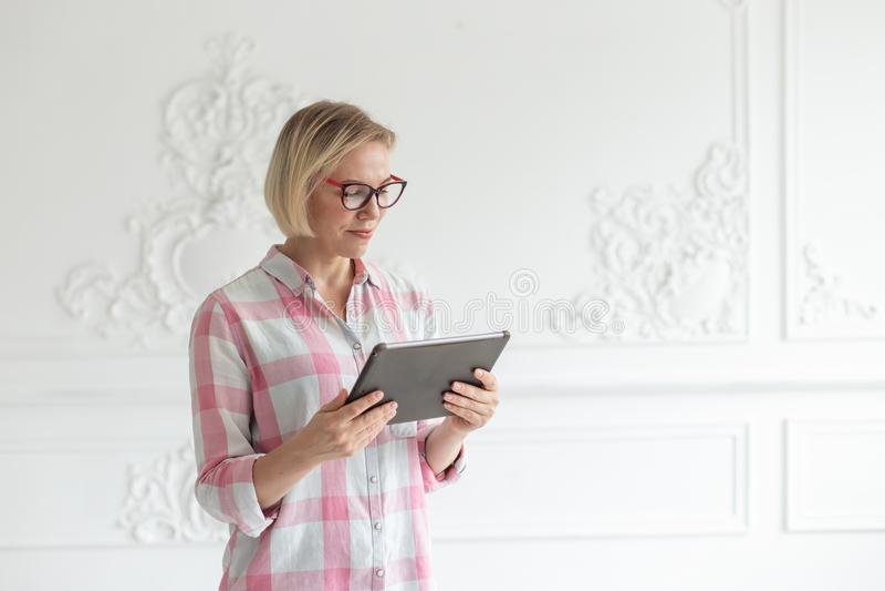 La mujer joven en vidrios lee el texto en su tableta imagenes de archivo